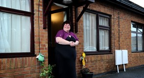 Tenant Clare stands outside her home